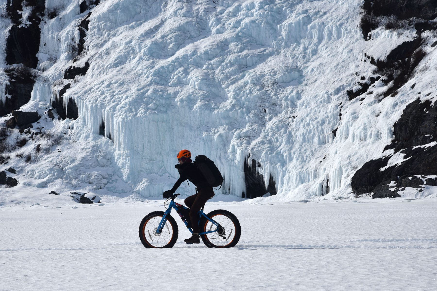 Cori biking past frozen waterfalls