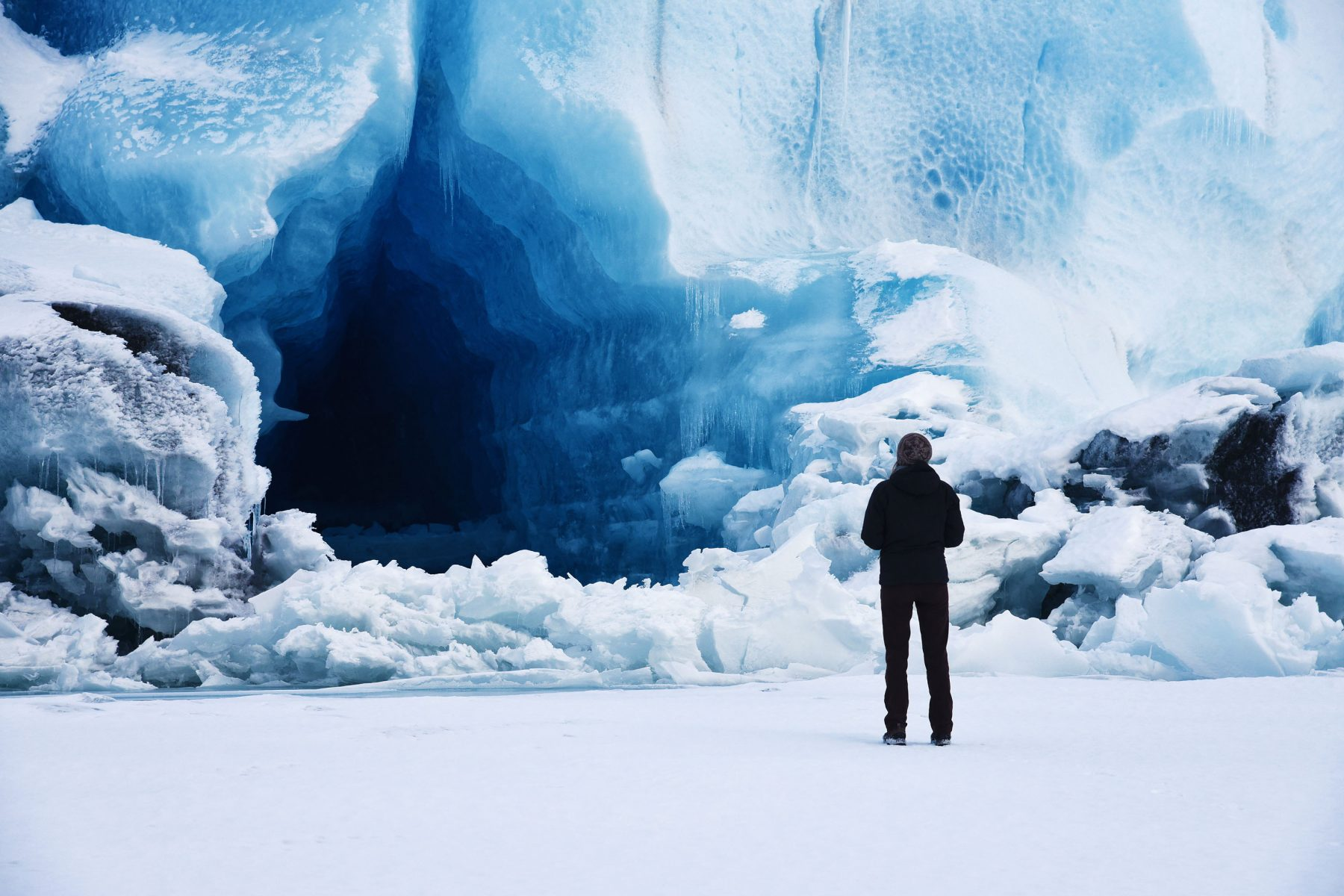 Cori standing outside a blue ice cave on Knik Glacier
