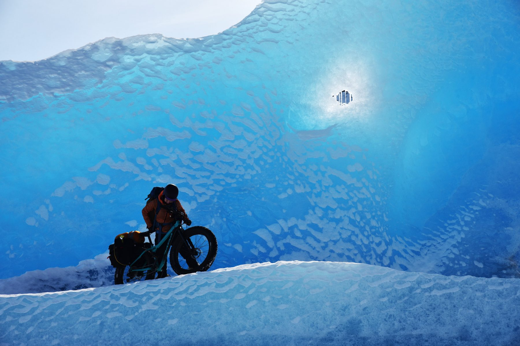 Devin Kelly pushing her bike up an iceberg at Knik Glacier