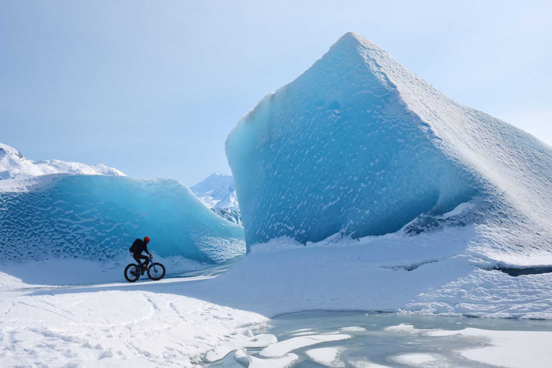 Cori Graves biking between icebergs in the Knik Glacier Canyon