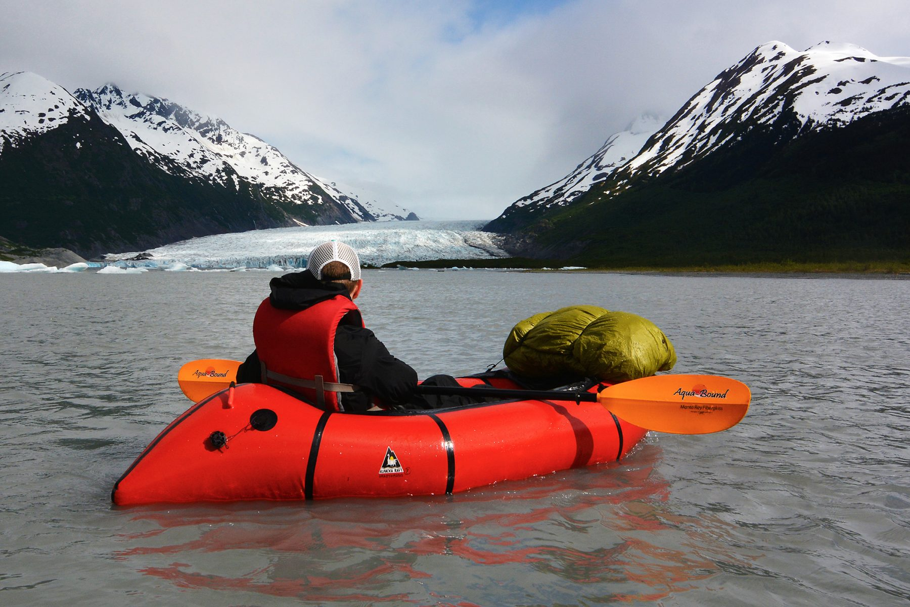Packrafter wearing an inexpensive life jacket below Spencer Glacier
