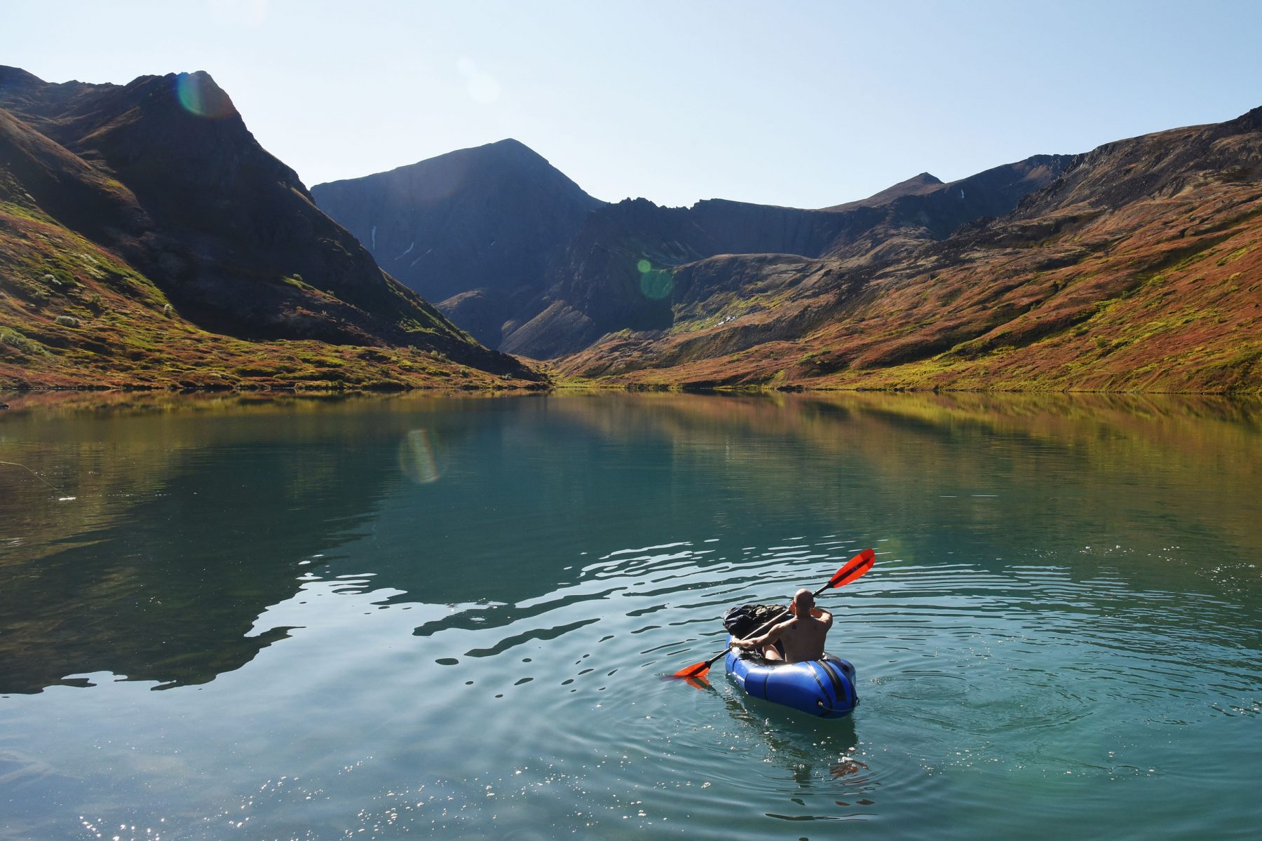 Greg Martin paddling an Alpacka Gnarwhal packraft across Symphony Lake