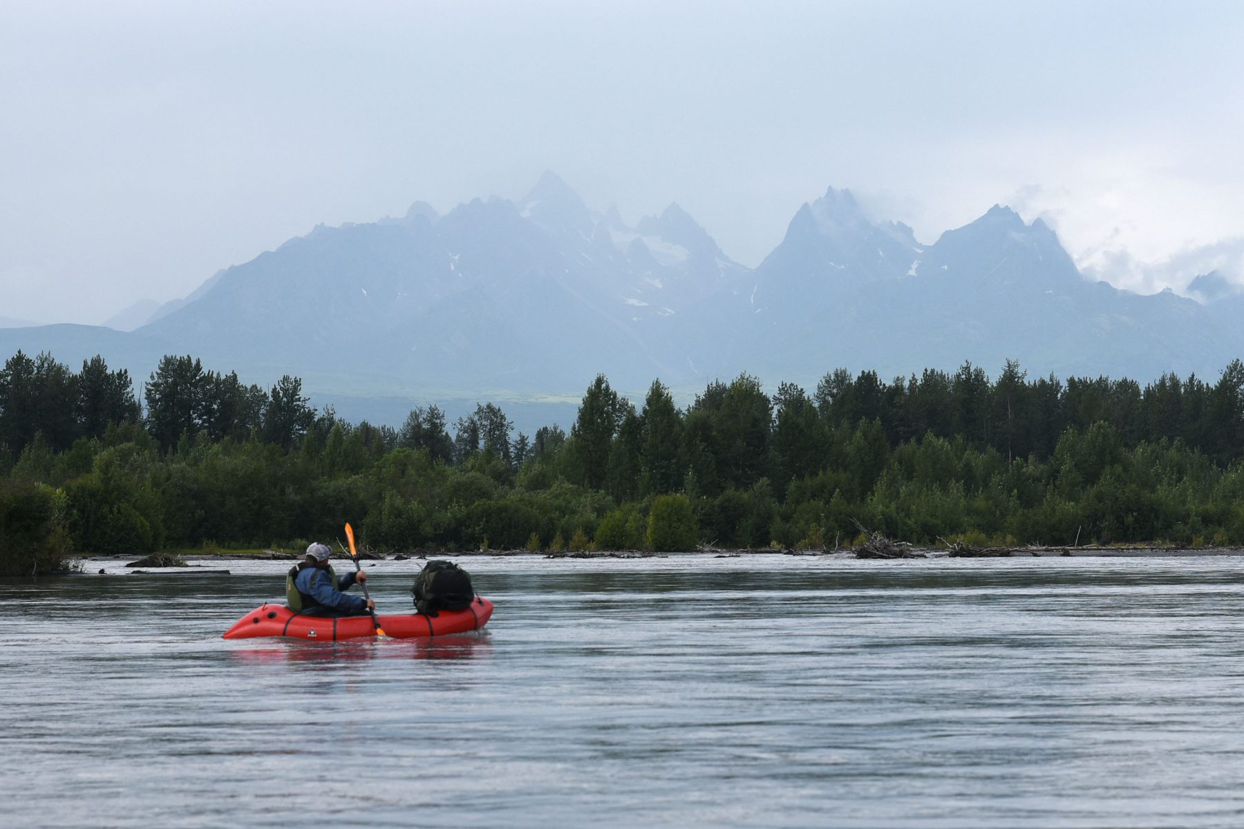 Brett Woelber packrafting past the confluence of the Tokositna and Ruth rivers